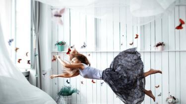 Mujer rodeada de mariposas sale por la ventana