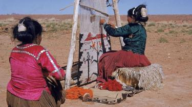 A Navajo woman weavers while another one watches