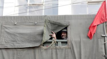 An Indian army soldier looks from the vehicle as they carry out a flag march during curfew in Jammu