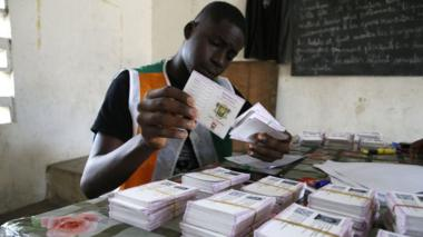 """An Ivory Coast Electoral Commission official holds voting cards during distribution of voting cards ahead of the country""""s presidential election that will be held on October 31, 2020 in Abidjan, Ivory Coast, 21 October 2020."""