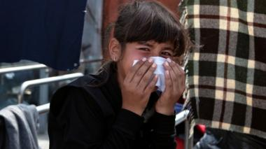 A girl reacts to tear gas fired by riot police