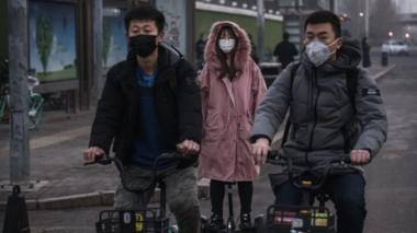 People wear protective masks as they ride in the street during the rush hour on February 10, 2020 in Beijing