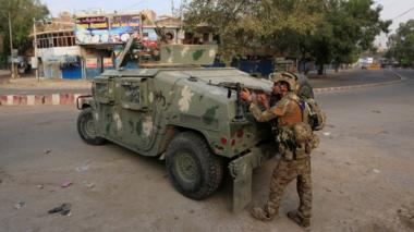 Afghan security forces keep watch near the site of an attack on a jail compound in Jalalabad