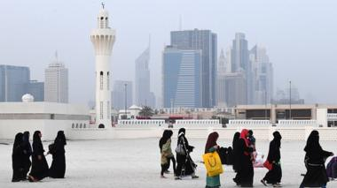 With Dubai's trademark skyscrapers in the background, Muslim women walk past a minaret