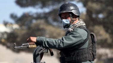 An Afghan security official stands guard on a road side check point in Herat, Afghanistan