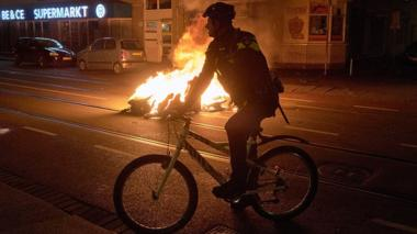 A police officer rides near a burning bin in The Hague, Netherlands