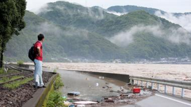 A man looks at the overflowing Kuma river in Yatsushiro, Kumamoto prefecture, 4 July