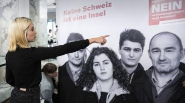 "Laura Zimmermann, one of the leaders of the ""no"" campaign, points to a poster"