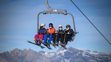 Skiers wearing protective face masks against the spread of the Covid-19, caused by the novel coronavirus, rides a ski lift before hitting the slopes in the Swiss ski resort of Verbier