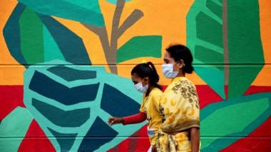 "Indian people walk past the graffiti depicting ""The story of coronavirus COVID19 pandemic'""to create awareness among people in Bangalore,"