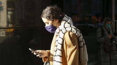 A woman wearing a protective mask reads her phone in New York
