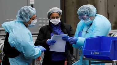 Hospital workers are seen near a tent erected to test for the coronavirus disease at the Brooklyn Hospital Center in Brooklyn