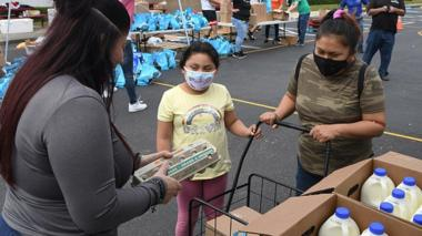 A woman and her daughter receive food assistance at a food distribution event in Orlando, Florida, 12 December 2020