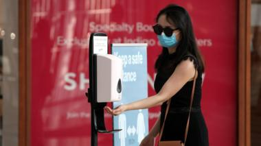 A woman wearing a face mask sanitizes her hand at Yorkdale Shopping Centre on July 7, 2020 in Toronto, Canada.
