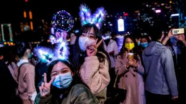 Women celebrate New Year's Eve with light-up bunny ears and festive lights