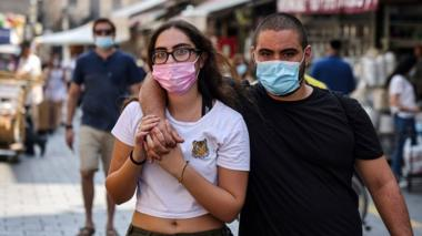 A couple, clad in protective masks, embrace while walking at the Mahane Yehuda market in Jerusalem on 17 September, a day ahead of Rosh-Hashana