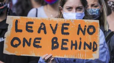 A demonstrator holds a banner reading 'LEAVE NO ONE BEHIND' as protesters gather to demand the immediate evacuation of Greek island refugee camps in Berlin