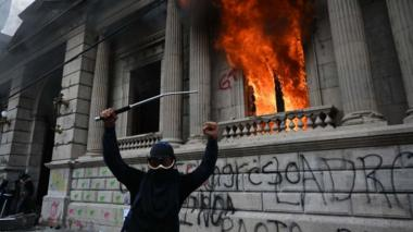 Demonstrators gesture after setting on fire an office of the Congress building during a protest demanding the resignation of President Alejandro Giammattei, in Guatemala City on November 21, 2020