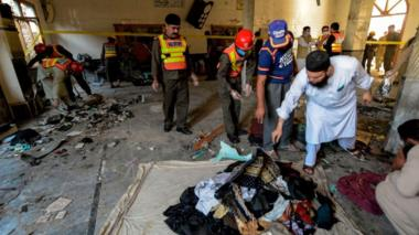 Rescue workers collect remains after a blast at a religious school in Peshawar on October 27, 2020