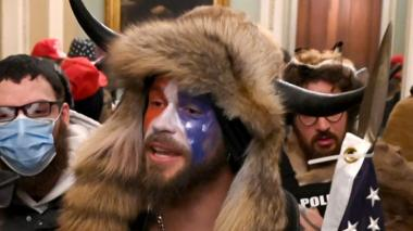 Jacob Anthony Chansley (C) is alleged to be the man seen wearing horns and a fur hat in photographs, including this from inside the Senate chamber