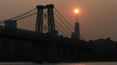 The sun sets behind the Manhattan Bridge and One World Trade Center in a haze created by smoke from the West Coast wildfires on September 15, 2020 in New York City .