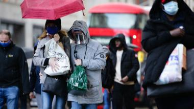 Shoppers wearing face masks, one also wearing a face shield, carry bags along Oxford Street in London