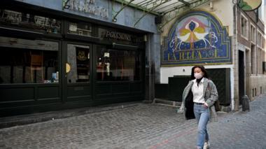 A woman in a mask walks past a closed restaurant in Brussels