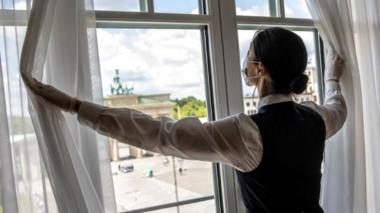 Housekeeper opening curtains in a Berlin hotel, May 2020