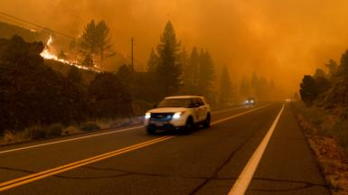 Vehicles drive down Highway 89 as the Tamarack Fire fills the sky with smoke. California 17 Jul 2021