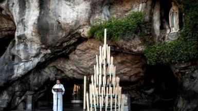 Rector Olivier Ribadeau Dumas conducts a small mass at the deserted Grotte de Massabielle in the Sanctuary of Our Lady of Lourdes on April 9, 2020 in Lourdes