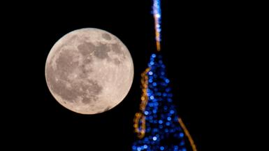 File photo from 30 November 2020, showing the full moon shining next to a Christmas tree in Mallorca