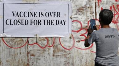 A man takes a photo of the notice stating ' Vaccine is over closed for the day' outside the gate of UNESCO vaccination center in Mumbai.