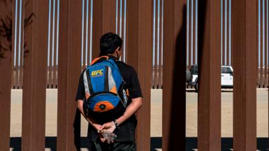 Man stands by US-Mexico barrier