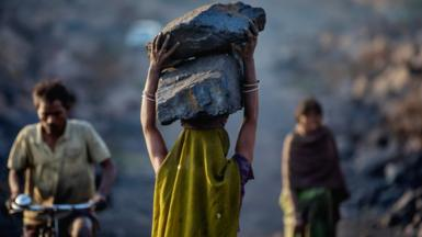 A female worker has piled coal on her head while she is working in Jharia coal field where a large amount of indias coal is mined. According to the World Economic Forum, in 2020, India was home to six out of 10 of the world's most polluted cities.
