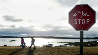 Two Inuit children return from school past a stop sign written in English and Inuit October 2002 in Iqaluit