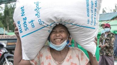 Woman in Myanmar carrying a sack of rice