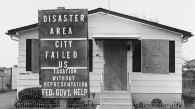 Boarded up house with sign saying 'disaster area'