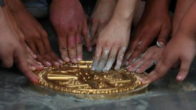 Several pairs of hands press down on a gold plaque that has been lain in the ground