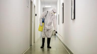 Man decontaminating a hallway