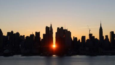 The sun rises above 42nd Street during a 'Manhattanhenge' sunrise or reverse 'Manhattanhenge' in New York City on 10 January 2021 as seen from Weehawken, New Jersey.