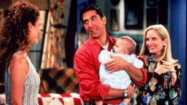 American actor David Schwimmer holds a baby, as actors Jessica Hecht (L) and Jane Sibbett look on, in a still from the television series, 'Friends in 1995