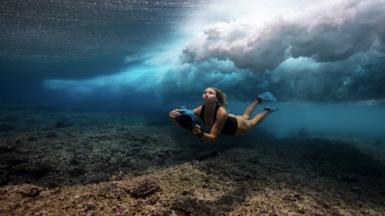 Woman freediving holding camera