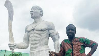 Monday Aigbe standing alongside a statue of his great-grandfather