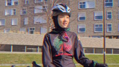 Masomah leaning on her bike
