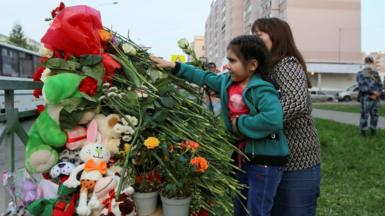People lay flowers at a makeshift memorial for victims of a deadly shooting at School No 175 in Kazan, Russia, 11 May 2021