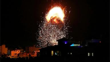 Flames rise above a building during Israeli air strikes in Gaza City May 17, 2021