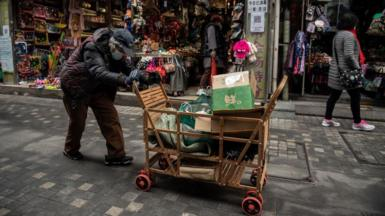 An elderly woman pushes a cart after searching through rubbish bins to collect recyclable items to sell, along a street near the Great Hall of the People in Beijing.
