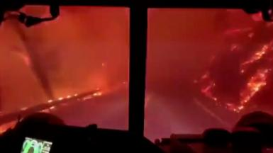 View as firefighters drive through fire
