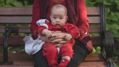 A woman holds a baby at a local park on 12 May 2021 in Beijing, China