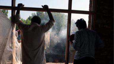 Kashmiris watch as people try to douse the fire at a damaged residential house where two alleged militants were killed in a military operation in Srinagar, Indian Administered Kashmir on 16 July 2021.